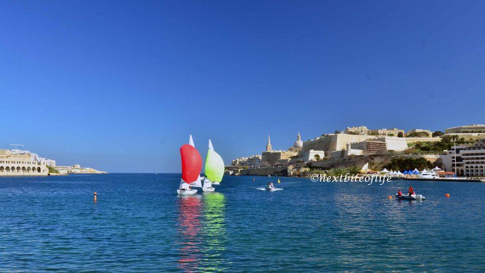 sailboats in sea in Malta yellow sail and green sail