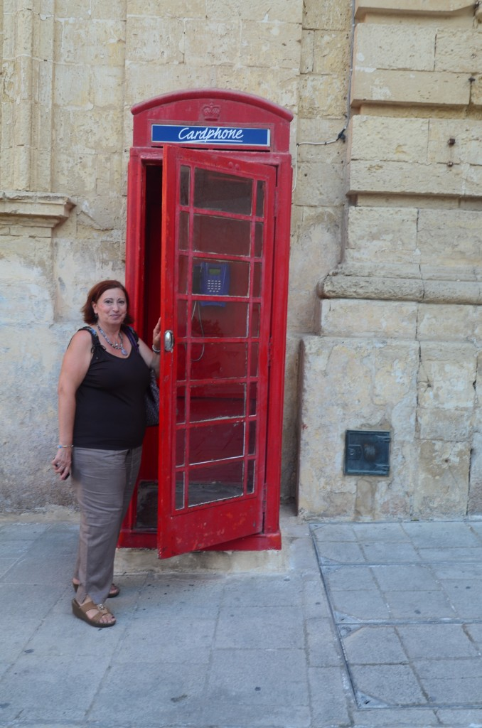 red phone booth in mdina malta with woman
