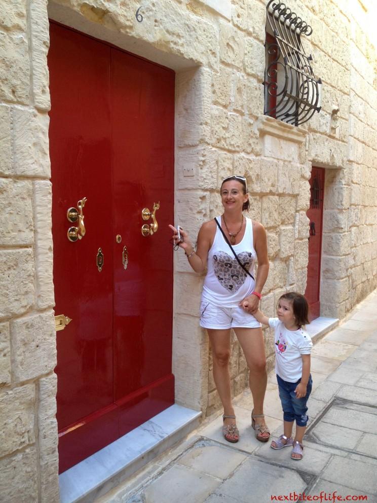Silent city Mdina - red door with mother and child admiring door knobs