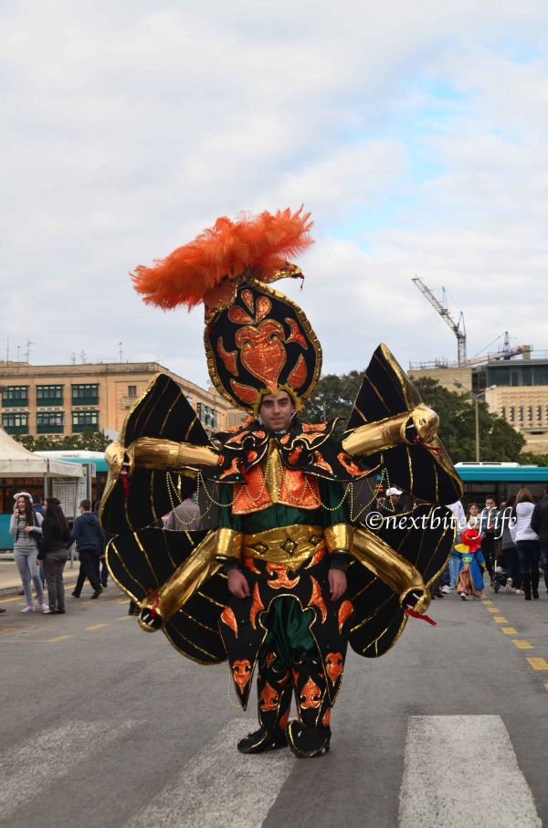 Man in black and orange carnival costume with orange headgear and gold arms
