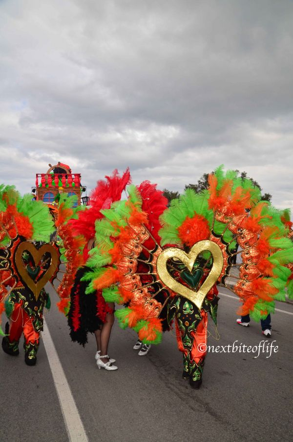 carnival costumes men and women with orange and green flowers