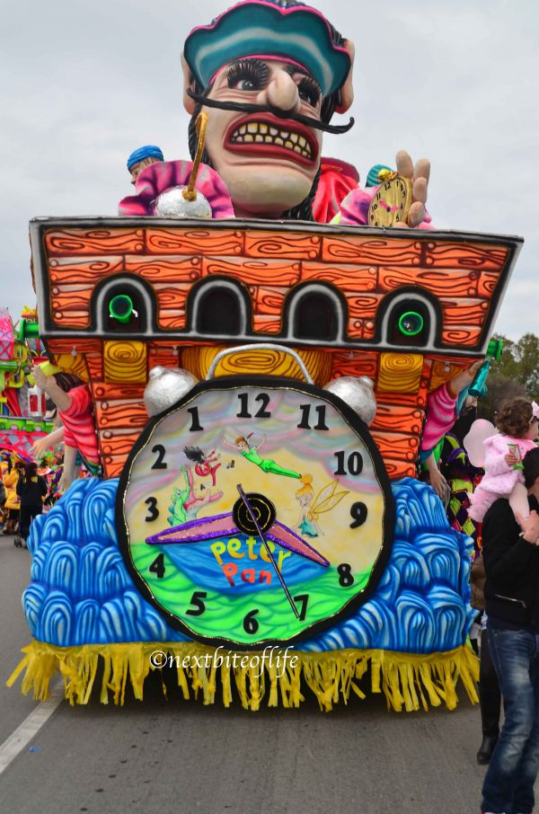 Malta carnival float with peter pan big clock in front. orange and blue