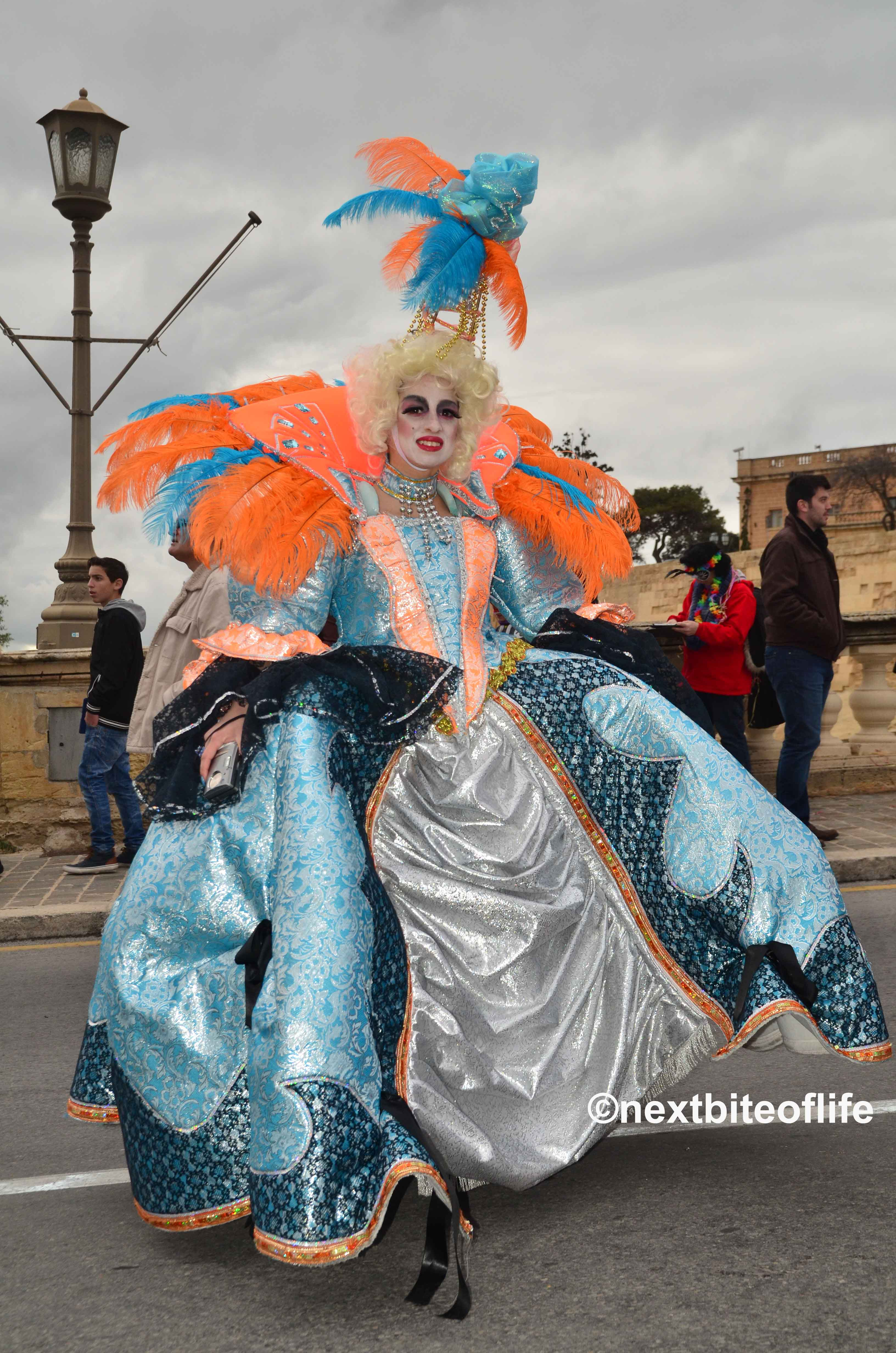 man in drag at the Malta carnival, blue dress with orange trim