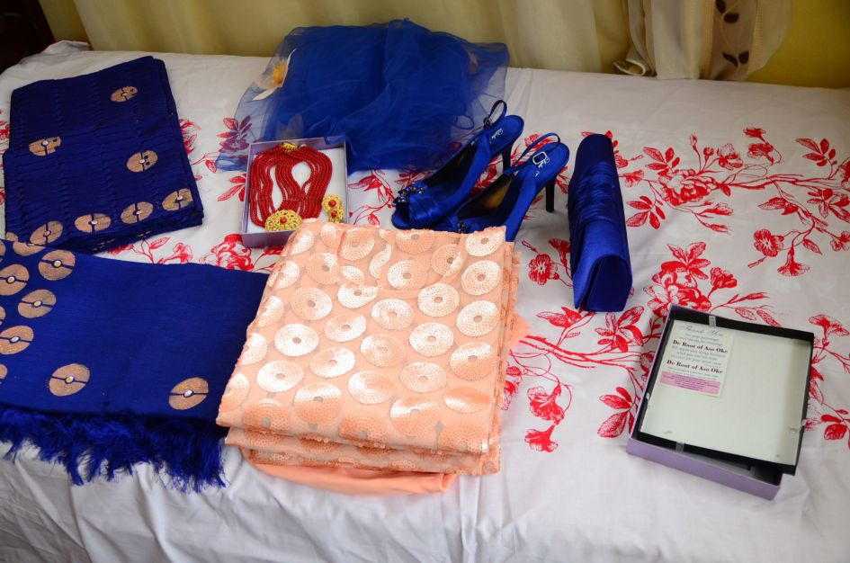 The bride's Nigerian native outfit laid out on bed  blue and orange colors