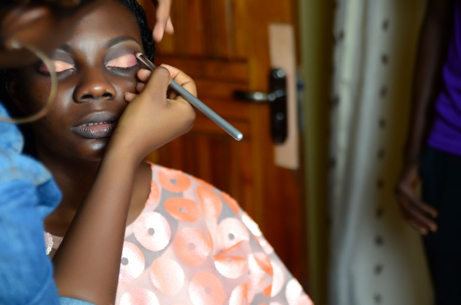 The warpaint being applied, bride's makeup in orange to match outfit