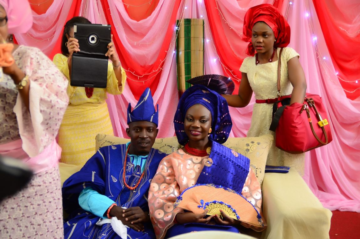 The engaged couple sitting and flanked by bridesmaids