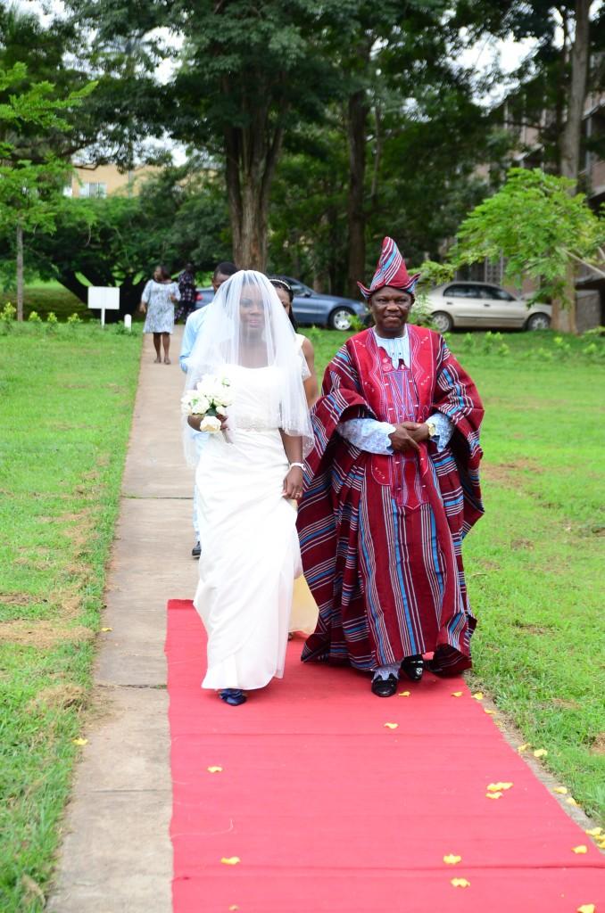 Nigerian wedding: bride and dad walking red carpet to church