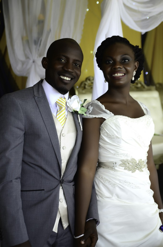 bride and groom smiling and holding hands at a Nigeria wedding in English attire