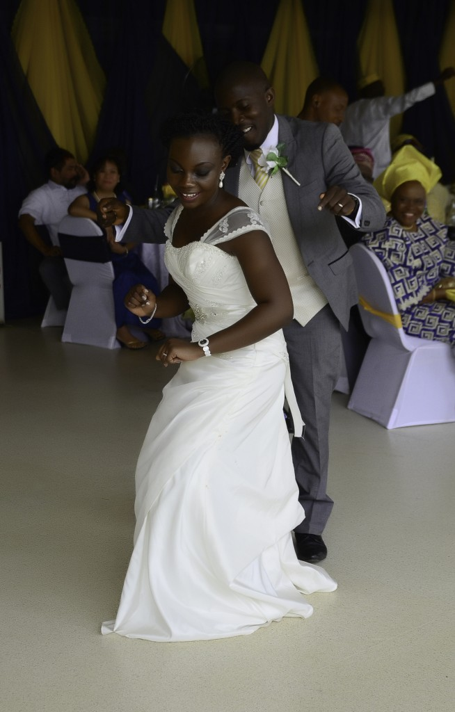Bride and groom dancing on a traditional Nigerian wedding. In English clothes, suit and white dress