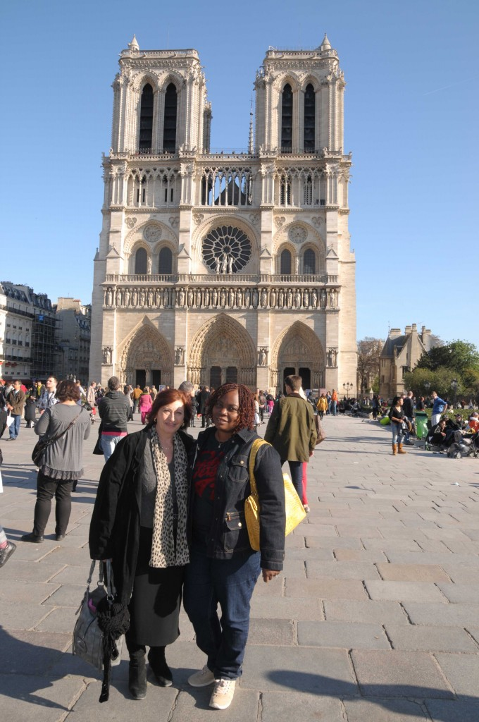 Notre Dame cathedral in Paris with 2 women posing.