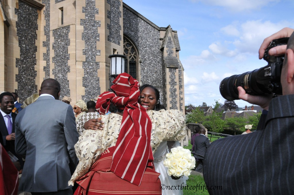 black bride being hugged by african attired mother
