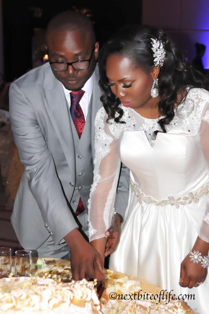 black couple cutting wedding cake