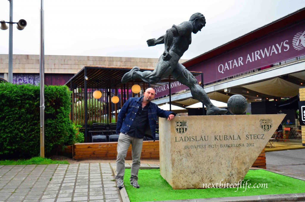 Kubala Stecz statue at camp nou barcelona with man posing.