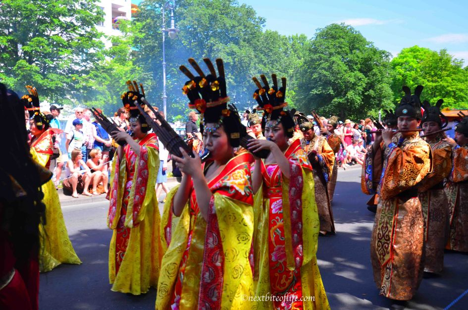 berlin carnival of culture. Women and men dressed in Kimonos and black headgear with 4 prongs