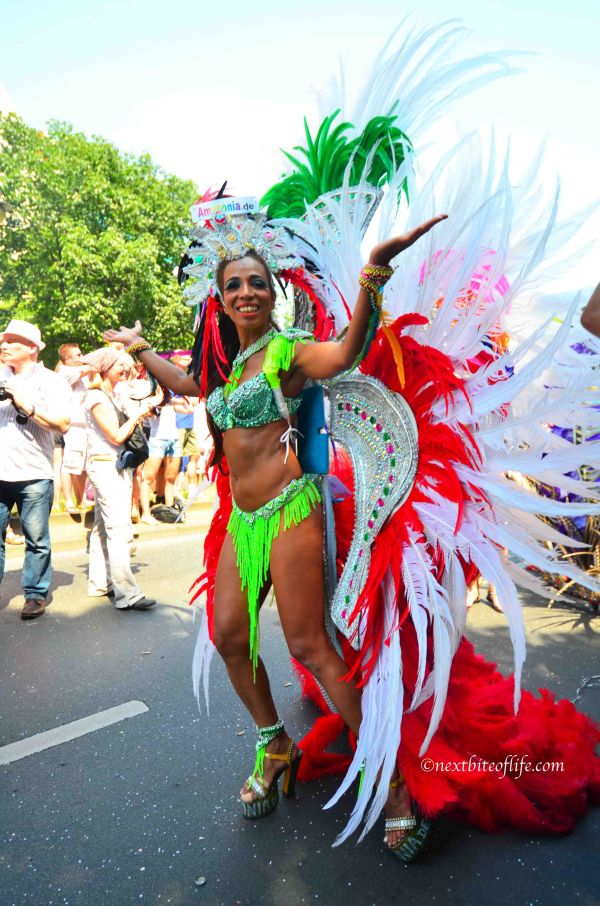 woman dressed in carnival attire..green bikini and red and white feather cpe