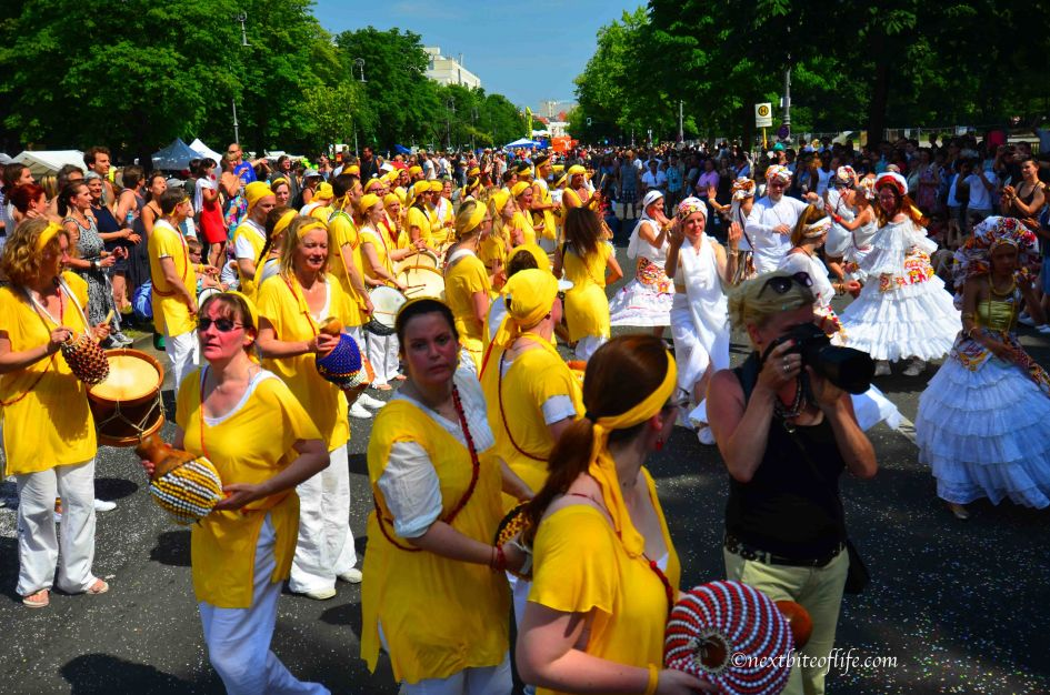 women in yellow holding marackas at parade