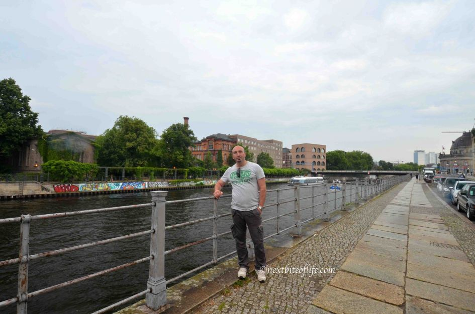 man on bridge and Spree river beside him with graffiti on the banks on berlin carnival of culture post
