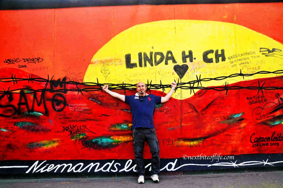 man posing at Berlin wall chain wire mural