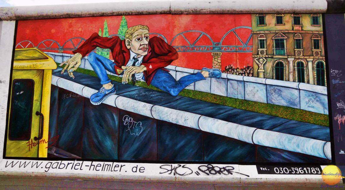 A man sneaking from Easte Berlin graffiti