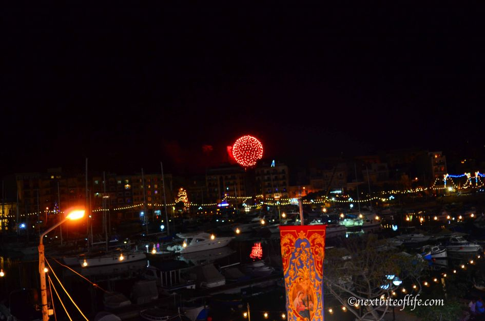 red fireworks being set off at Msida marina Malta