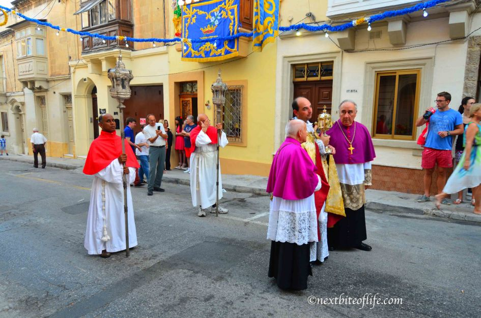 priests dressed up and carrying staff on street in Malta for St. Joseph day