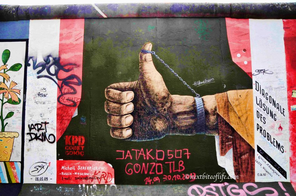 Russian writing on the Berlin wall showing a man with thumbs up and chain tied to thumb from wrist