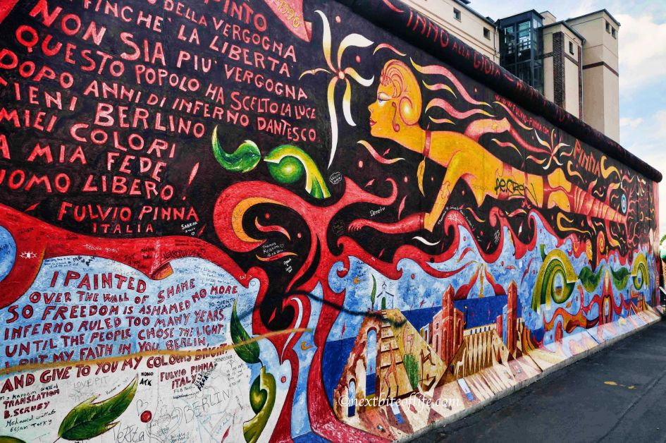 Mural of the Berlin wall remains showing graffiti writing in Spanish in red and black