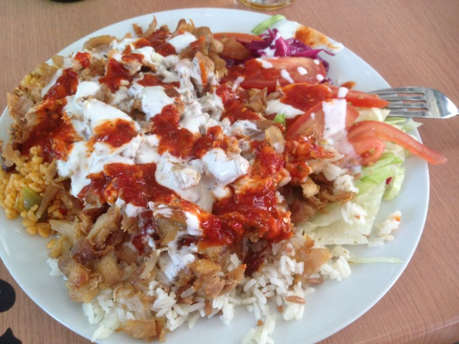 a plate of food in Budapest - rice topped with lettuce,chicken, white and red sauce and tomatoes