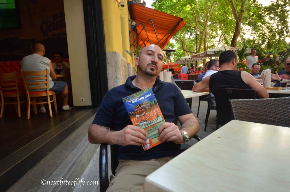 man holding hooters menu in Budapest outside tables