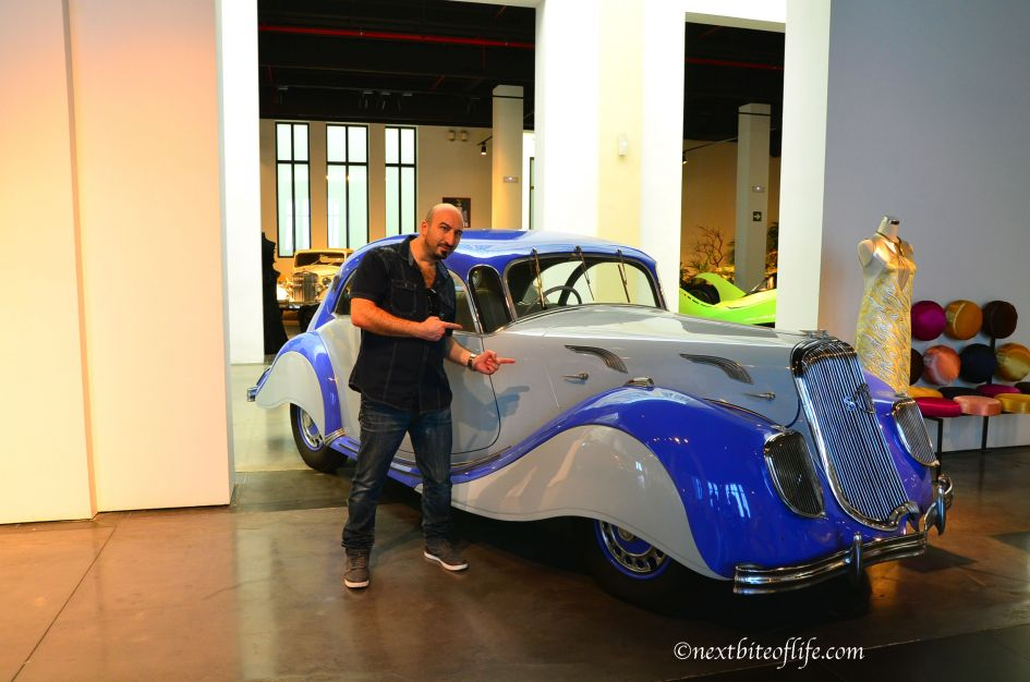 man posing in front of classic blue and grey car at museum automovilistico in Malaga Spain