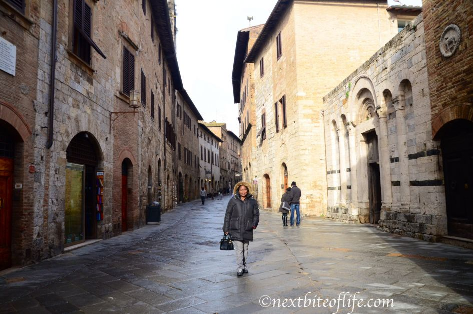 woman in black coat in San Gimignano Italy