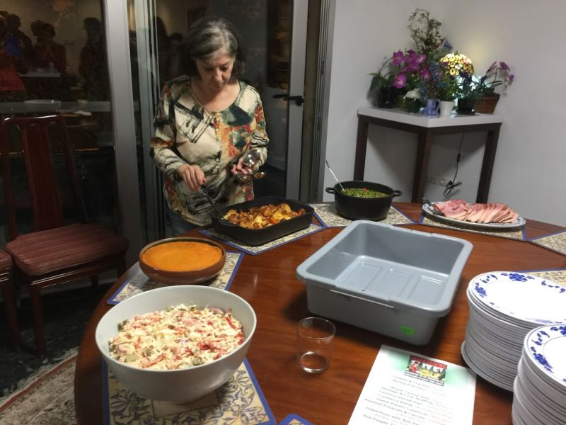Woman in front o round table with slaw and potatoes