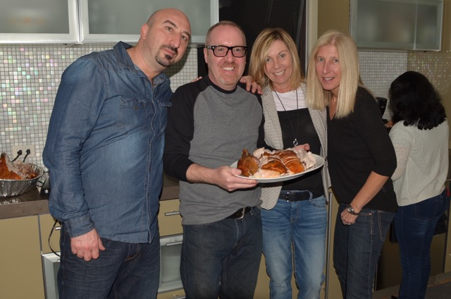 4 people posing with turkey plate in hand