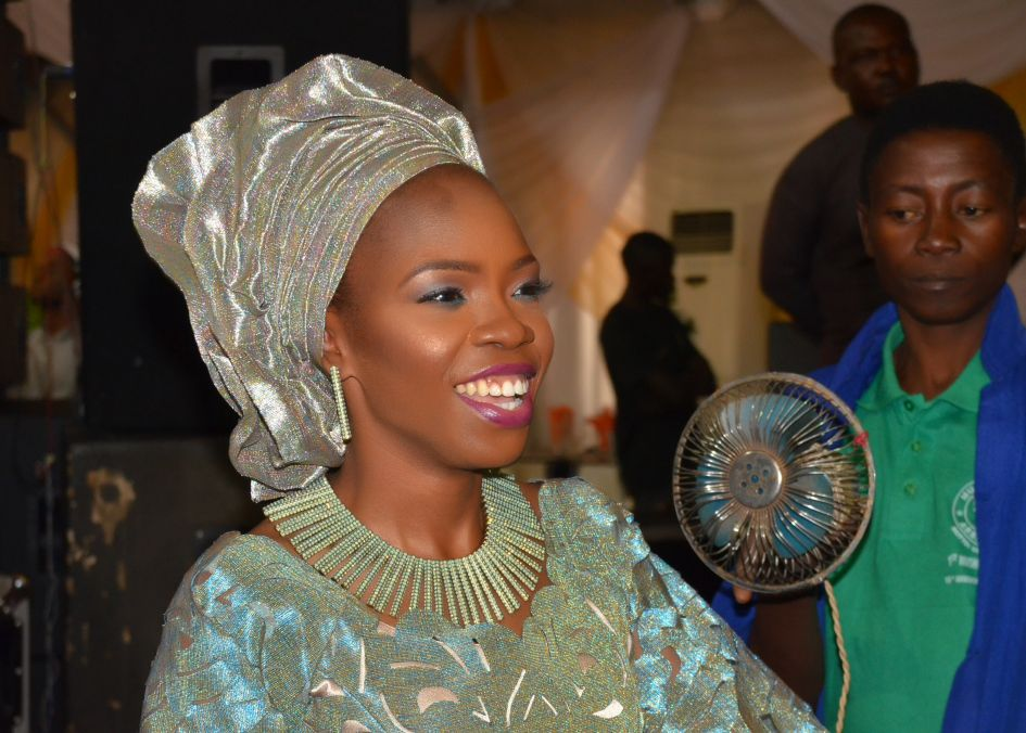 image of Nigerian bride in wedding attire and head gear silver and teal colors