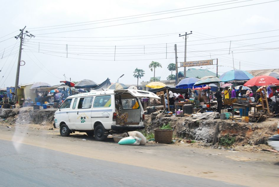 markets scene Nigeria with white van being loaded with goods on side street