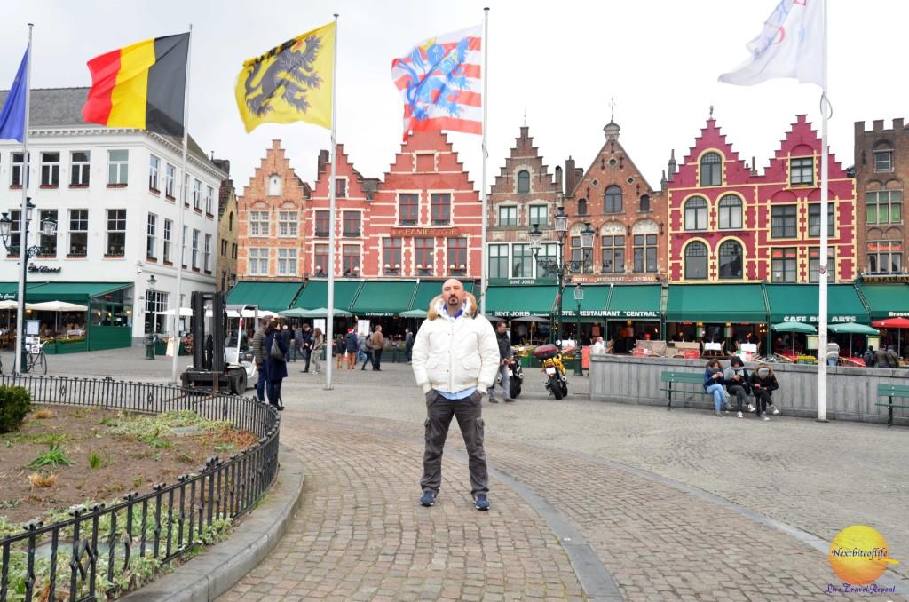 dam square bruges belgium with guy posing