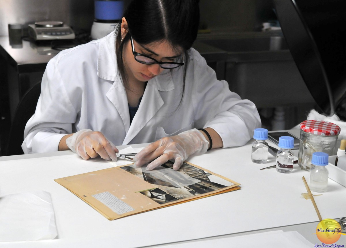 She is restoring an old photograph.