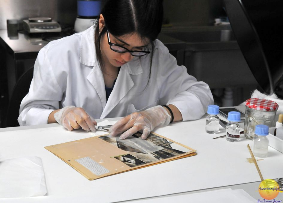 She is restoring an old photograph. Woman in lab coat at MNAC
