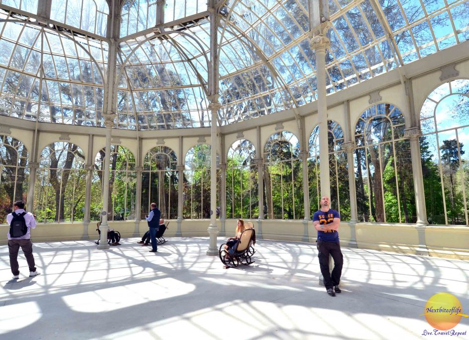 at the El Retiro Park Crystal Palace interior showing man leaning on poles and women in chairs rocking