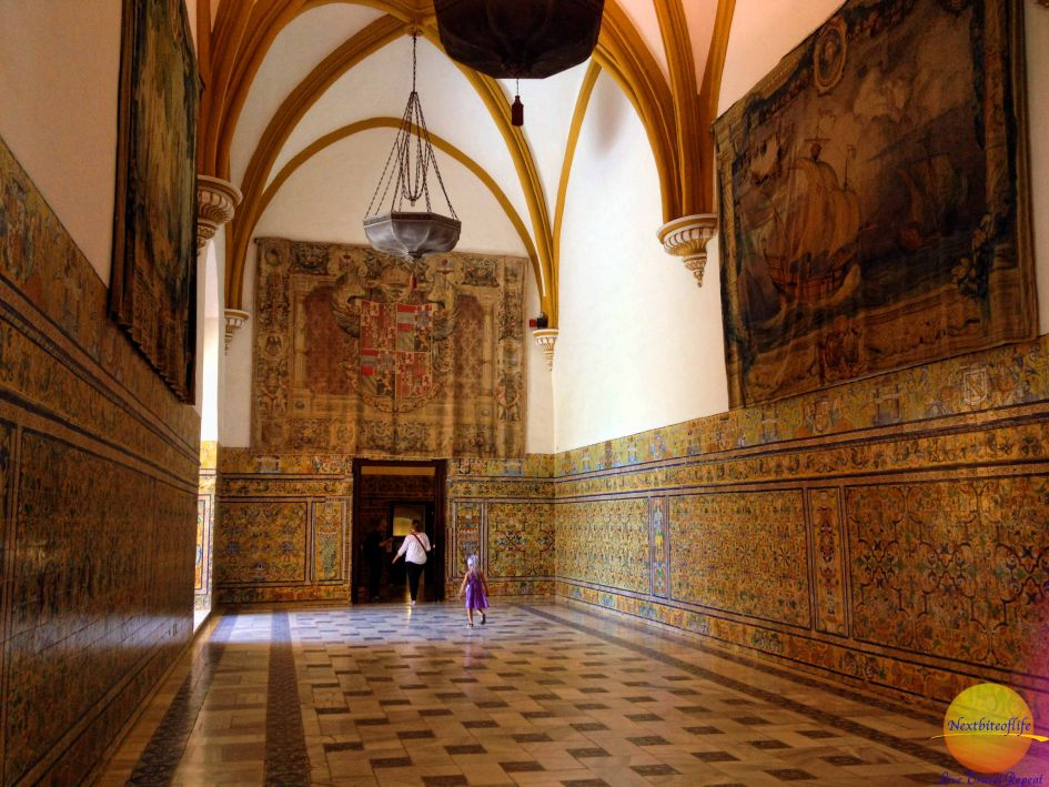 alcazar hall in Seville with decorated tiles on walls