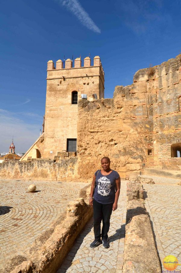 woman posing in Carmona fortress showing tower behind her #carmona #fortress #carmonfortress #sevilledaytrip #andalusia