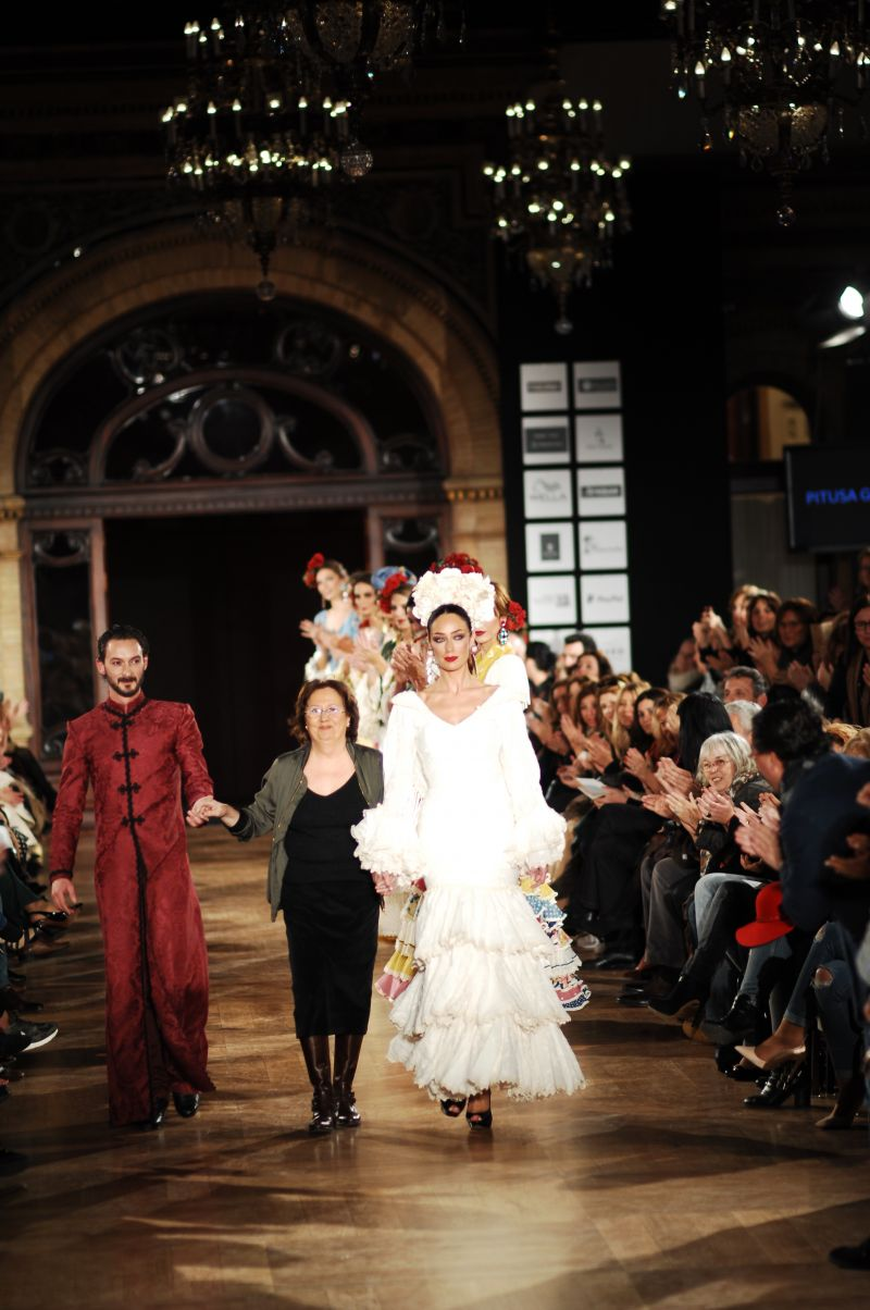 One of the designers of the flamenco gowns being led on stage at flamenco show end...