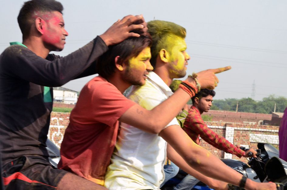 3 young men in face paint on motorcycle hindu festival