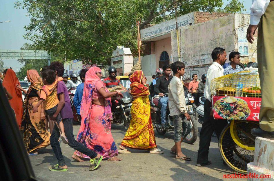 women walking on the streets of delhi for hindu festival.