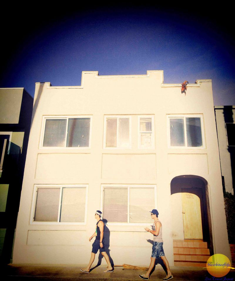 two guys walking past a house on the venice beach boardwalk