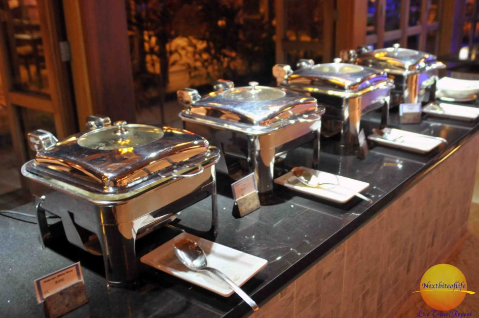 covered pans with food at buffet