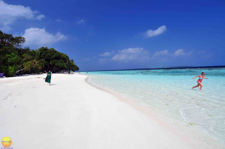 vilamedhoo beach seen, girl running,lone woman walking and few people in the sea.