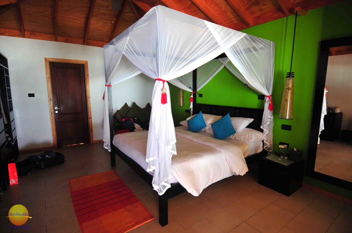 beach villa room at vilamendhoo resort with mosquito net.