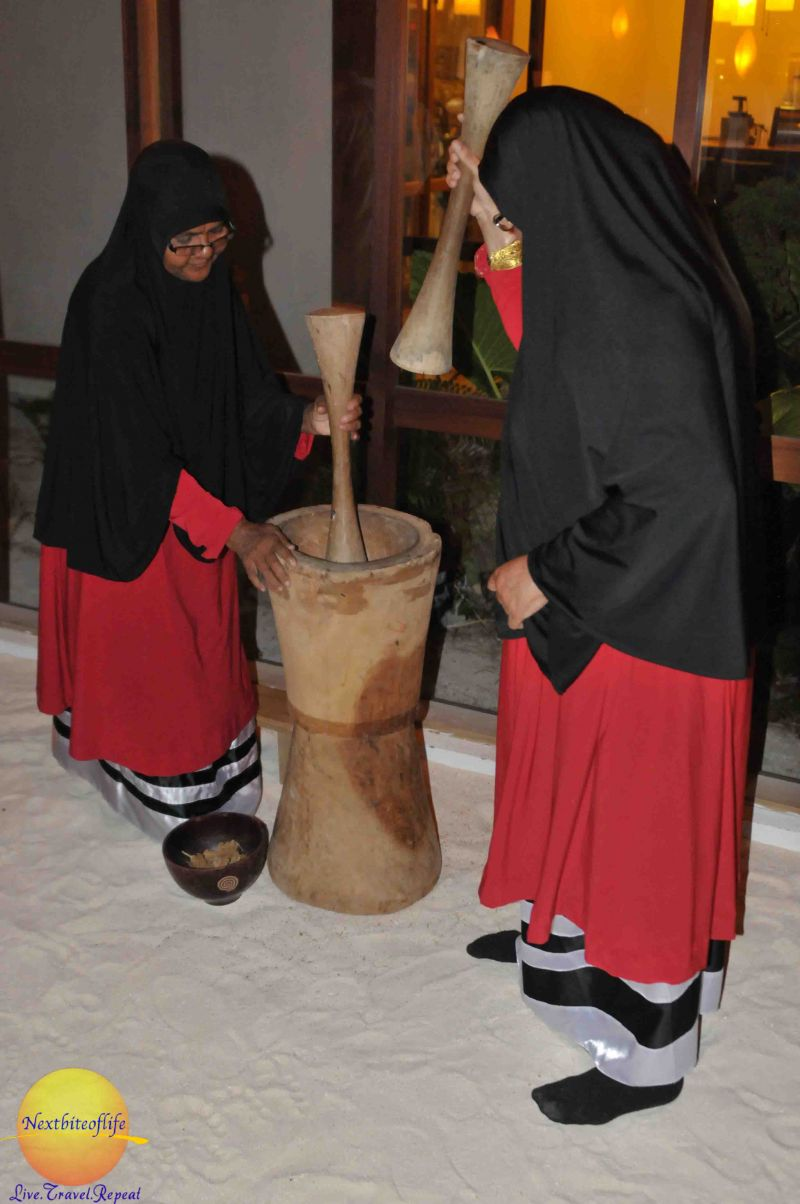two Maldivian women pounding leaves