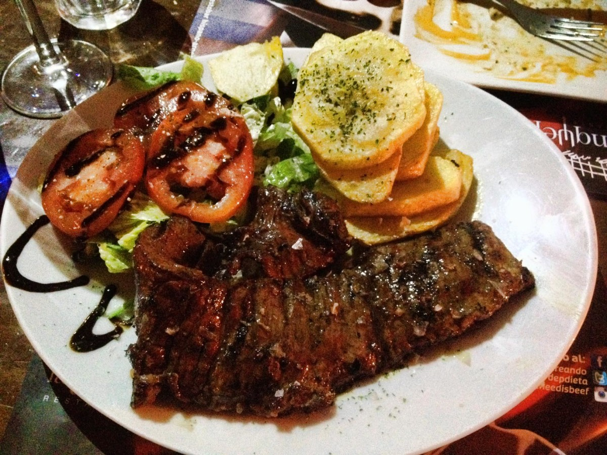 plate of argentinian steak with salad and potatoes